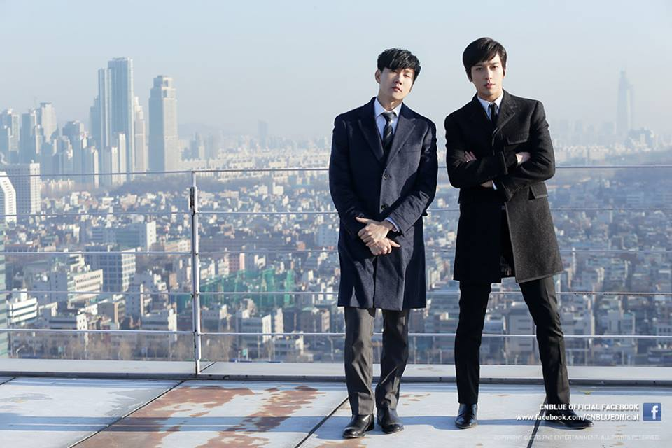JJ Lin and Yonghwa pose coolly on top of a building