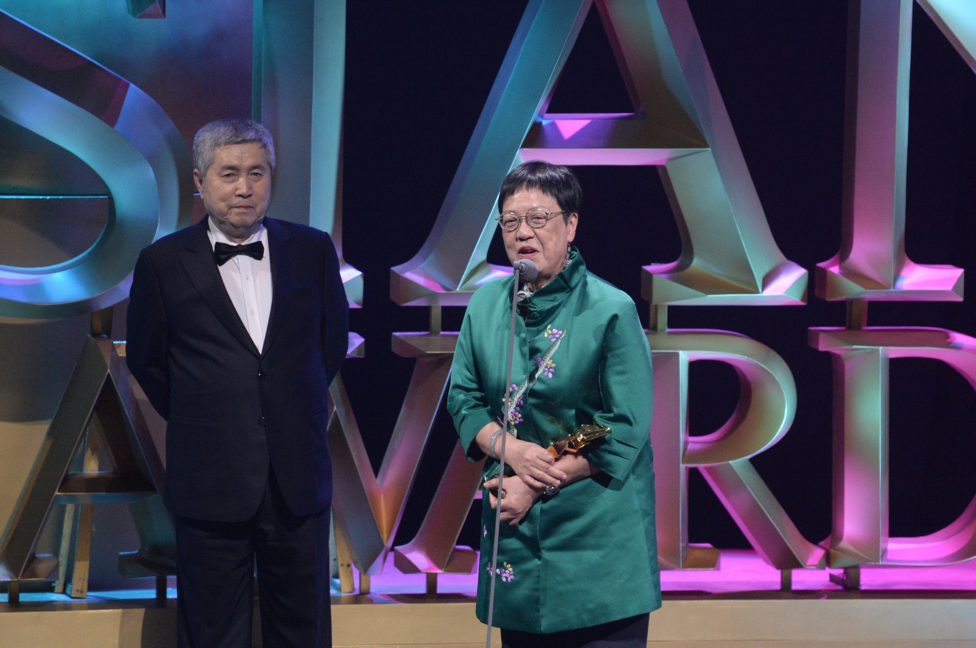 Renowned director and Lifetime Achievement Award recipient Im Kwon-taek hands over the Best Director award to Ann Hui for 'The Golden Era' at the 9th Asian Film Awards