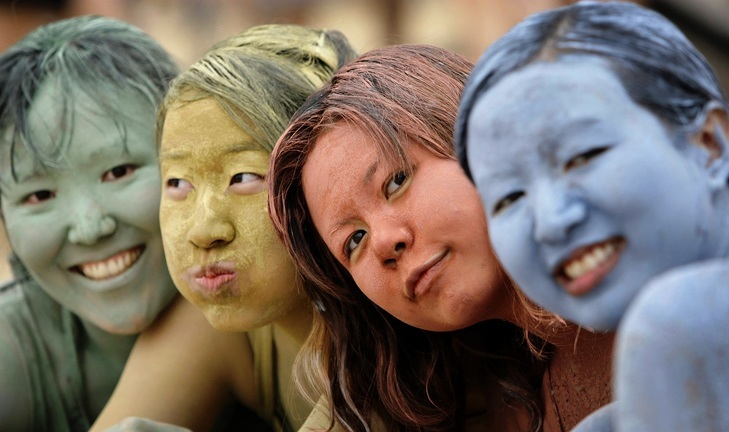 Asian tourists make up with color mud during the Boryeong Mud Festival on Daecheon Beach in Boryeong, south of Seoul, South Korea, Saturday, July 11, 2009. The 12th annual mud festival features mud wrestling, mud sliding and a mud king contest. (AP Photo/ Lee Jin-man)