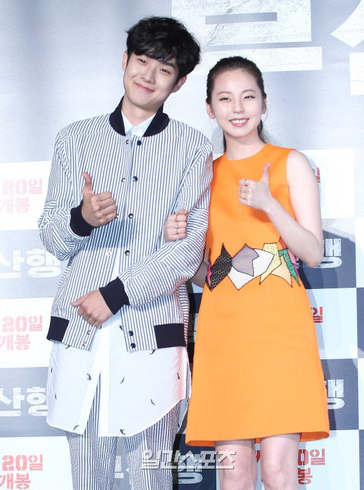 "Image: Actors Choi Woo Sik and Sohee giving a thumbs up to the press during conference for film ""Train to Busan"""