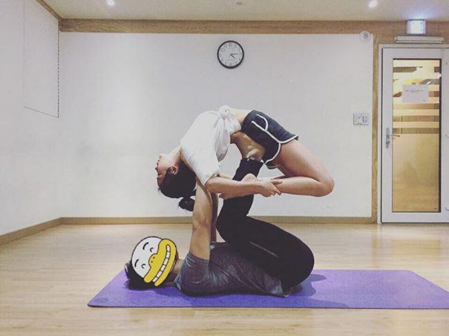 Image: Hyunyoung in the middle of a yoga exercise with the help of her instructor / @cho_hyunyoung
