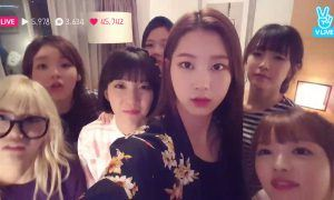 Image: Oh My Girl streaming live on V App while a mysterious figure looms behind them from outside