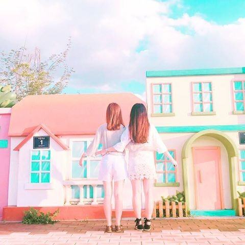 Two friends standing in front of an adorable, Candyland-esque building at the Bicycle Park in Jeungpyeong. / Dispatch