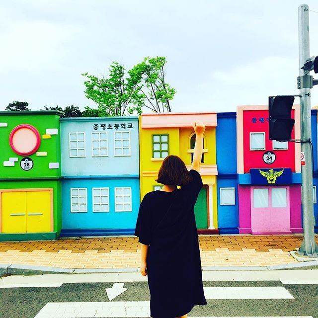 "Tourist standing in front of another ""street"" of adorable, mini town buildings at the Bicycle Park in Jeungpyeong. / Dispatch"