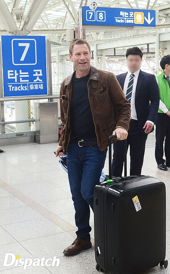 Aaron Eckhart smiling at the media who greeted him at the train station / Image source: Dispatch