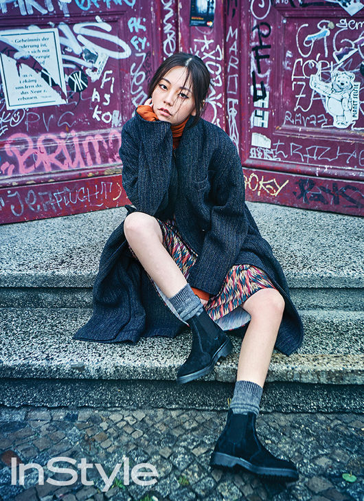 Ahn Sohee coolly posing in front of a graffiti-filled wall, sitting on a gray step in Berlin, Germany