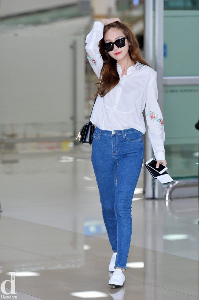 Jessica rocks a simple, but feminine outfit at the airport in light-blue jeans and a flowery white shirt.
