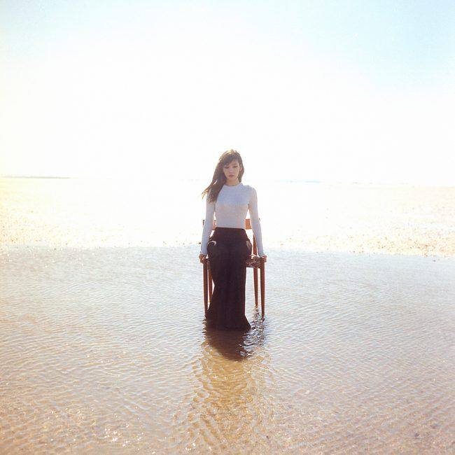 Taeyeon looks elegant as she sits on a chair, surrounded by water / Image source: SM Entertainment