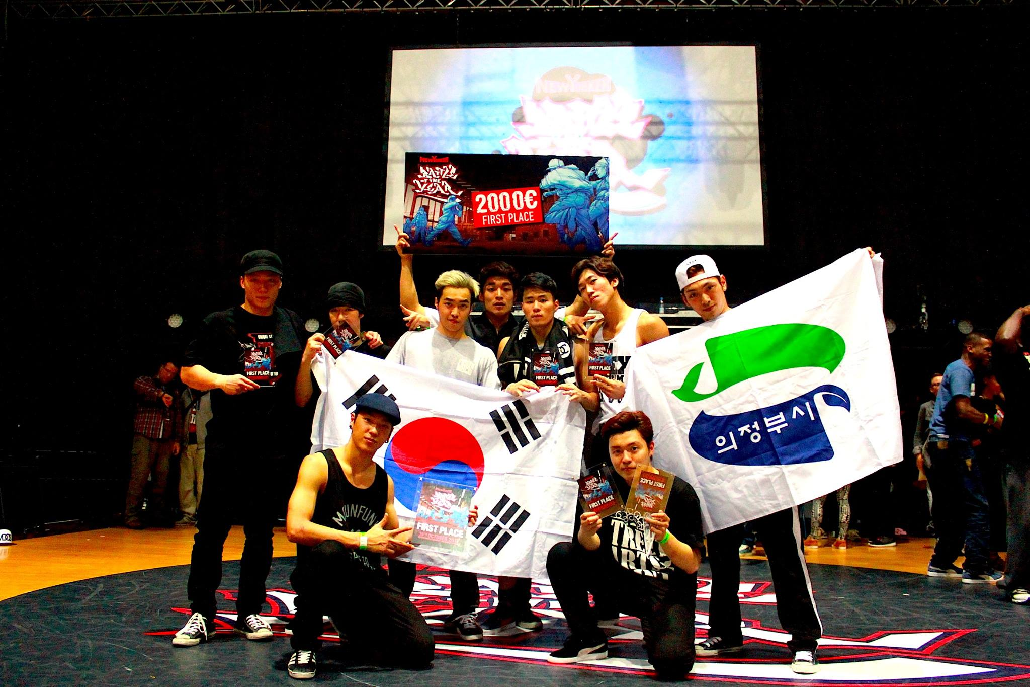 B-Boy Krops who is on the bottom right is holding two 1st place trophies