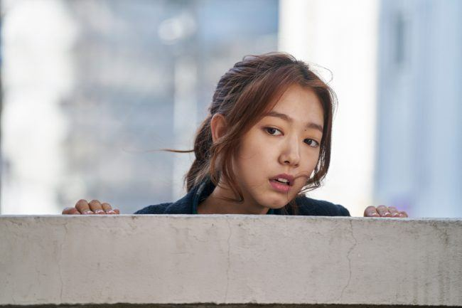 Actress Park Shin Hye peeking over a wall at someone for Hyung movie still/ Image Source: CJ Entertainment