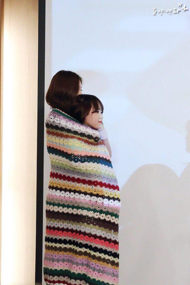 The girls look adorable rolled up into a blanket.