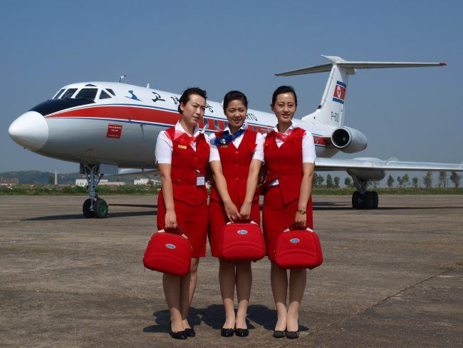 Stewardesses wearing the old Air Koryo red uniform.