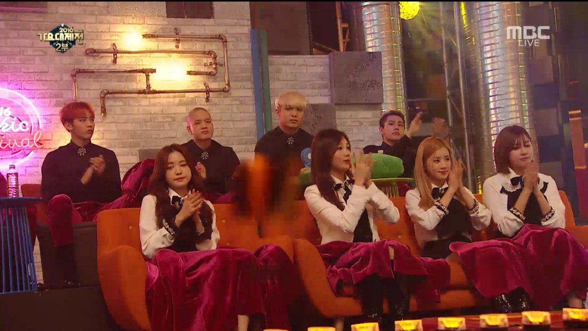 Apink sitting down with BTOB's jackets on their laps