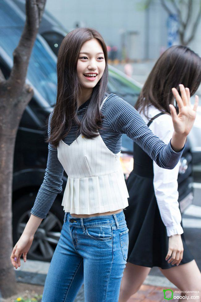 Doyeon sports a cropped stylish white peblum tanktop layered over a long sleeved shirt.