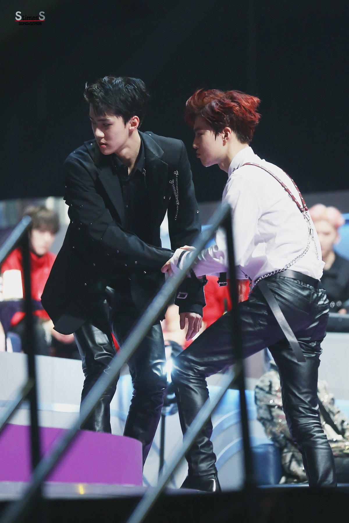 Suho advised Sehun to sit down while he makes the offer to sit on the edge of the long couch.