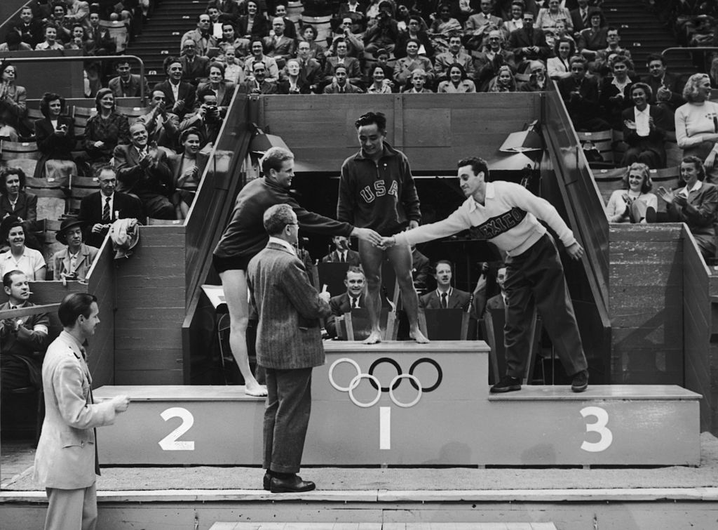 5th August 1948: Olympic medal ceremony at the Empire Pool, Wembley. Men's Platform Diving, Bruce Harlan (USA) second congratulates Joaquin Capilla Perez (Mexico) third and Samuel Lee (USA) winner. (Photo by Topical Press Agency/Getty Images)