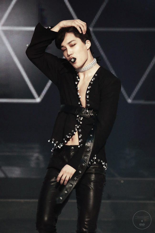Kai seductively reveals his toned chest as he dances in his embellished suit and diamond choker.