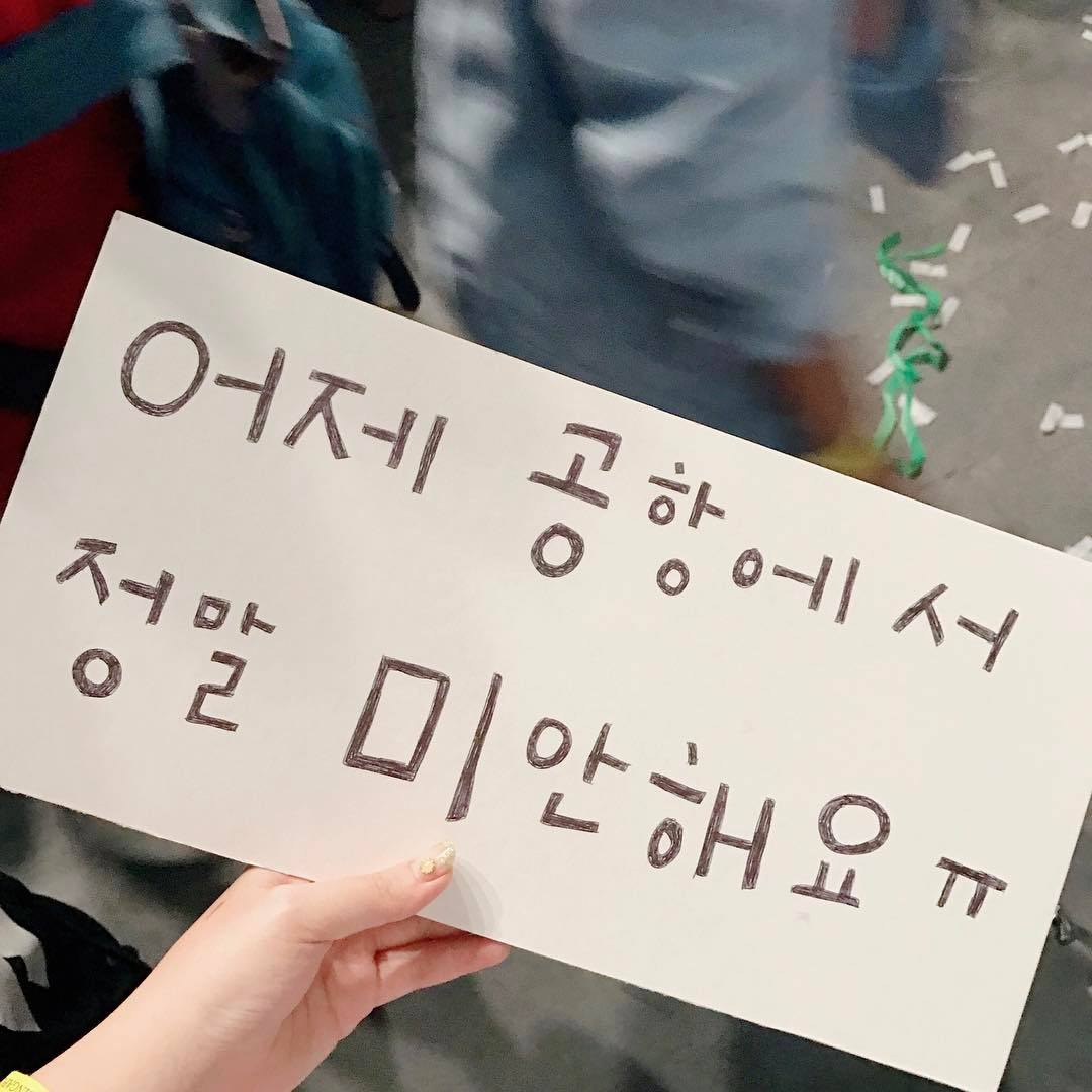 """Sorry [for what happened] at the airport"" apology sign written by a fan"